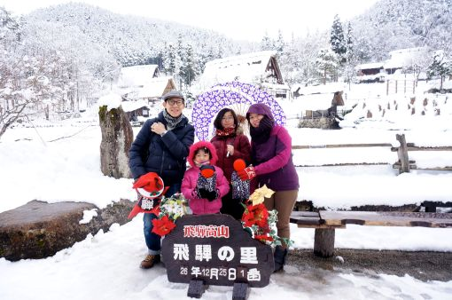 """Christmas portrait in Hida Folk Village. The little dollies we were holding are called """"Sarubobo"""", little charms that ward off evil spirits. Girls were so enamored with them and insisted on buying quite a number!"""